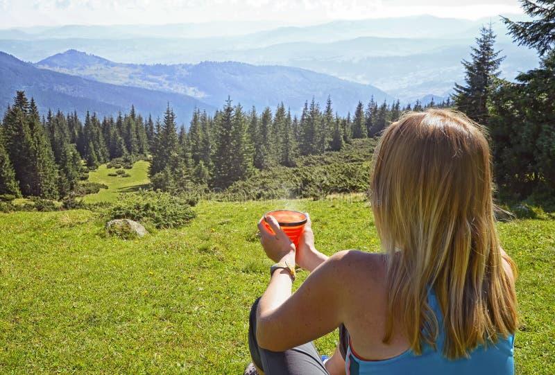有茶的年轻女人,咖啡,坐草 免版税库存图片