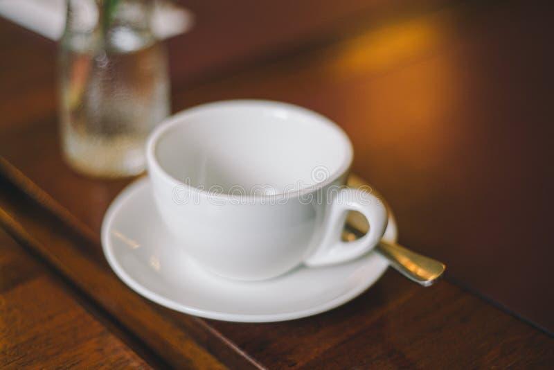 有茶碟和匙子的特写镜头空的白色杯子在桌上 库存照片