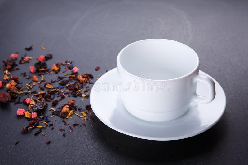 有茶碟的茶杯在黑背景 与瓣、干莓果和果子的混合物草本花卉果子茶 免版税库存照片