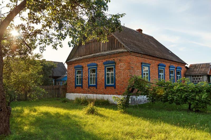 有草坪的简单的砖村庄房子在日落日出的围场在乡下的宁静 免版税库存图片