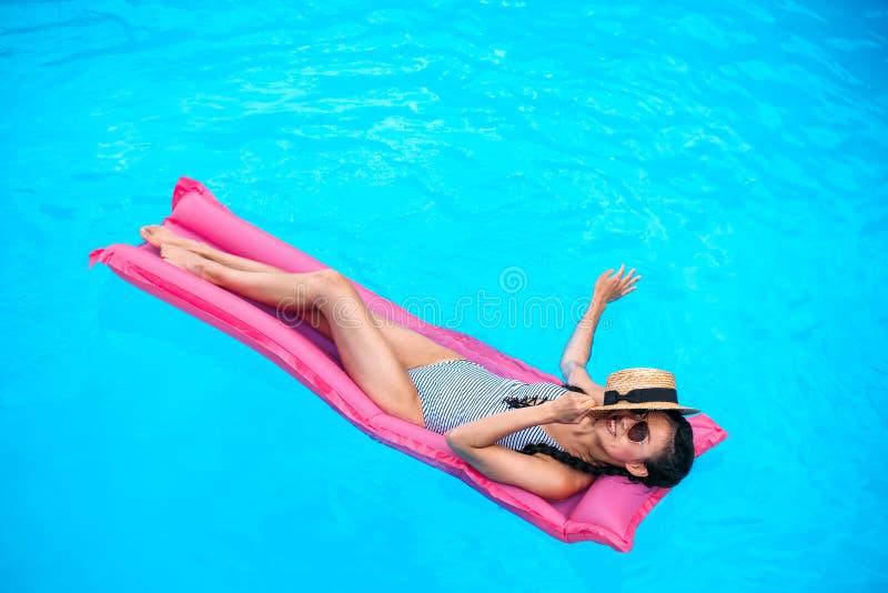 有草帽漂浮在可膨胀的床垫的覆盖物面孔的年轻亚裔妇女 免版税库存照片