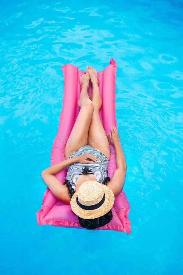 有草帽漂浮在气垫的覆盖物面孔的少妇 免版税库存图片