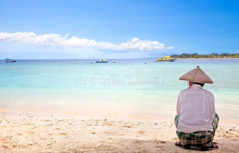 有草帽的印度尼西亚人坐海滩 免版税库存图片