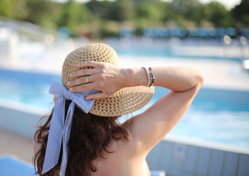 有草帽的妇女在专属豪华旅游胜地晒黑 库存图片