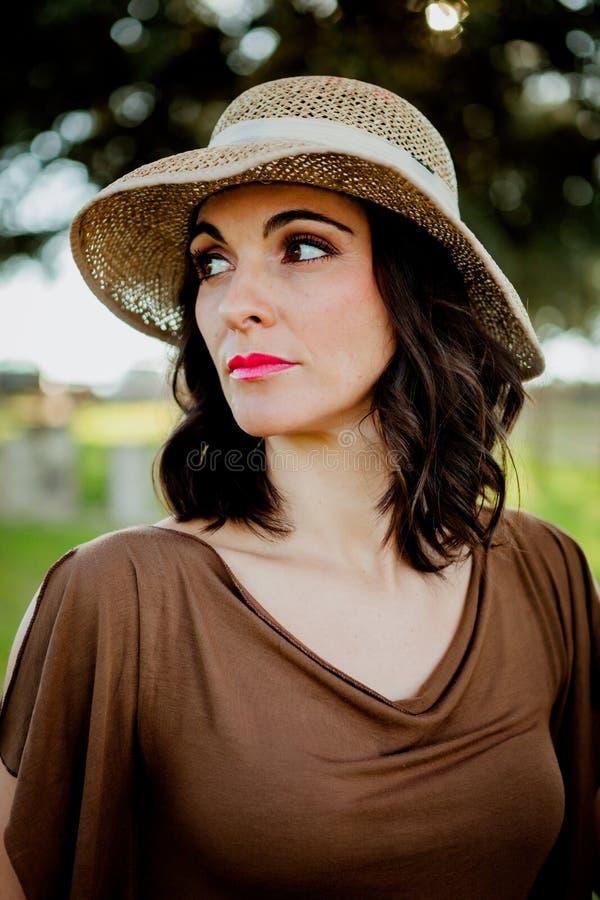 有草帽的时髦的少妇 库存照片