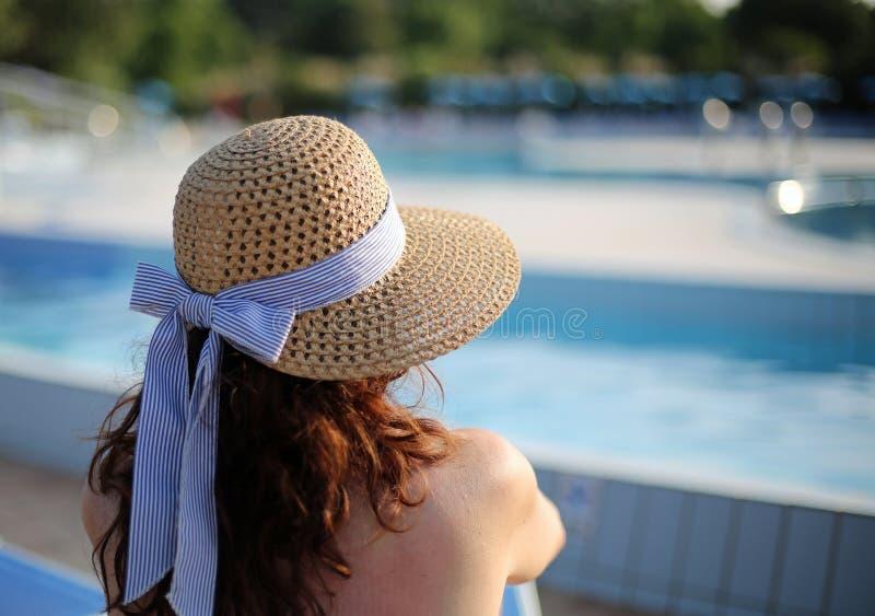 有草帽的美丽的妇女在专属luxuriou放松 免版税库存图片