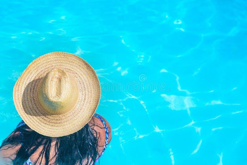 有草帽的美丽的性感的妇女在有自由空间的蓝色清楚的游泳场 暑假概念 免版税库存照片