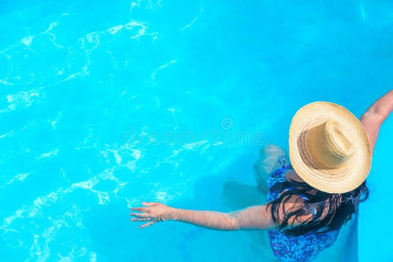 有草帽的美丽的性感的妇女在有自由空间的蓝色清楚的游泳场 暑假概念 免版税库存图片