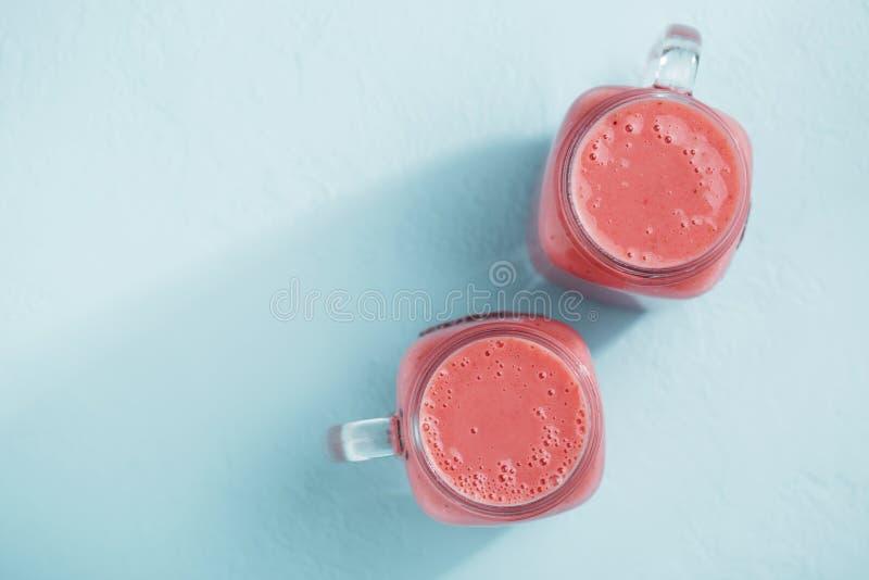 有草莓圆滑的人的两个金属螺盖玻璃瓶在蓝色淡色背景 库存照片