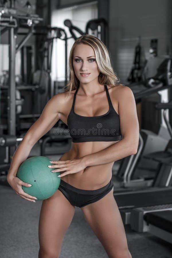 有药丸的白肤金发的妇女在健身房 免版税库存照片