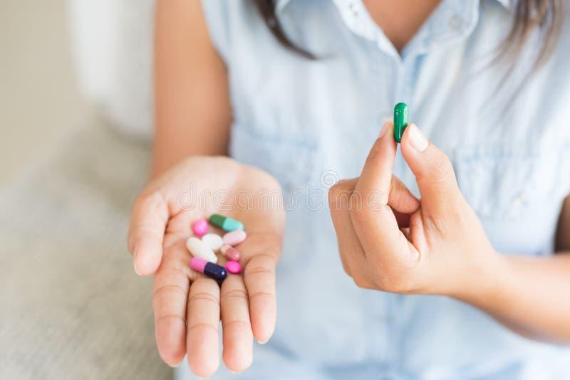 有药片医学片剂的妇女手和胶囊在她的手上 库存照片