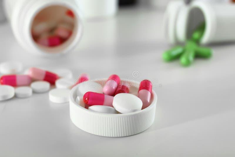 有药片的塑料盖帽在桌上 免版税库存照片