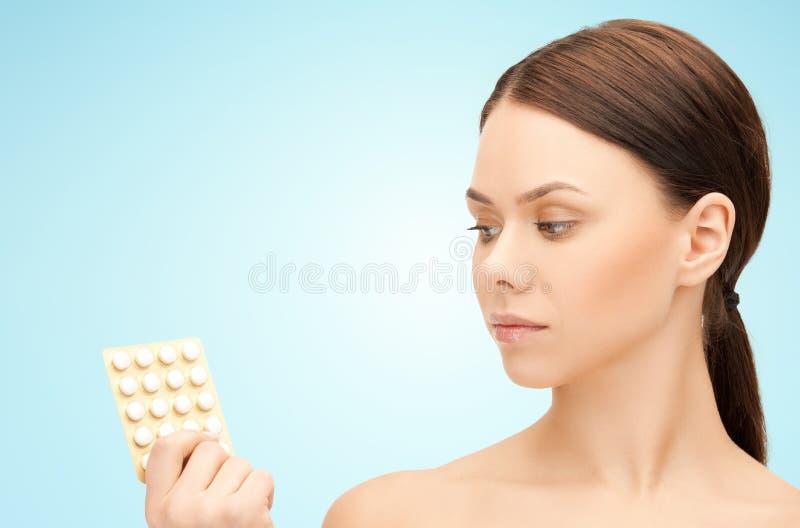 有药片的年轻女人在蓝色背景 免版税库存图片