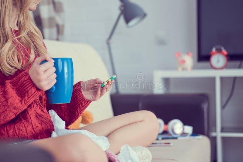 有药片的病的女孩和茶坐沙发 免版税图库摄影