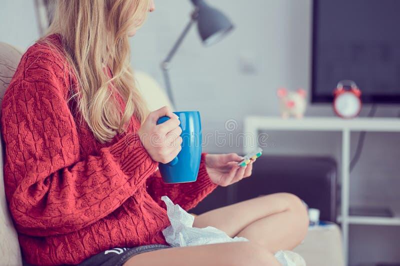 有药片的病的女孩和茶坐沙发 库存图片