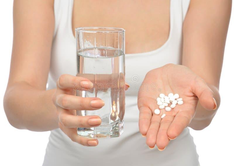 有药片医学片剂和杯的妇女手水 免版税库存照片