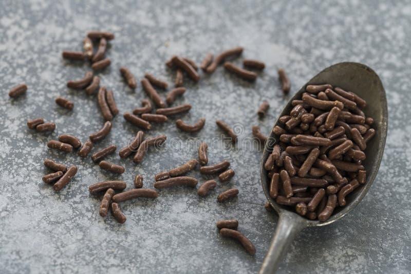 有荷兰巧克力冰雹的黑暗的金属匙子,在具体厨房梳妆台 免版税库存图片