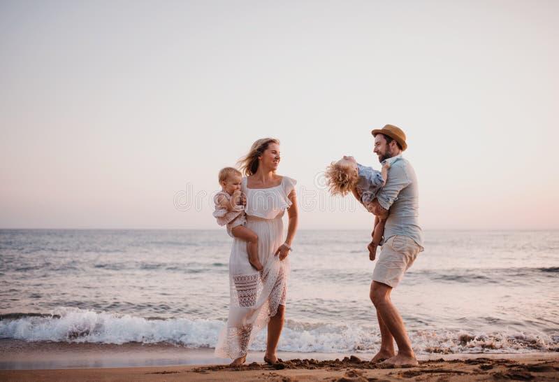 有获得两个小孩的孩子的一个年轻家庭在海滩的乐趣在度假夏天休假 库存图片