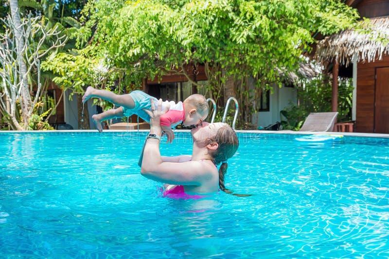 有获得乐趣和游泳在水池的八个月的一个小孩子的妈妈 r 妇女亲吻她的小他 免版税库存照片