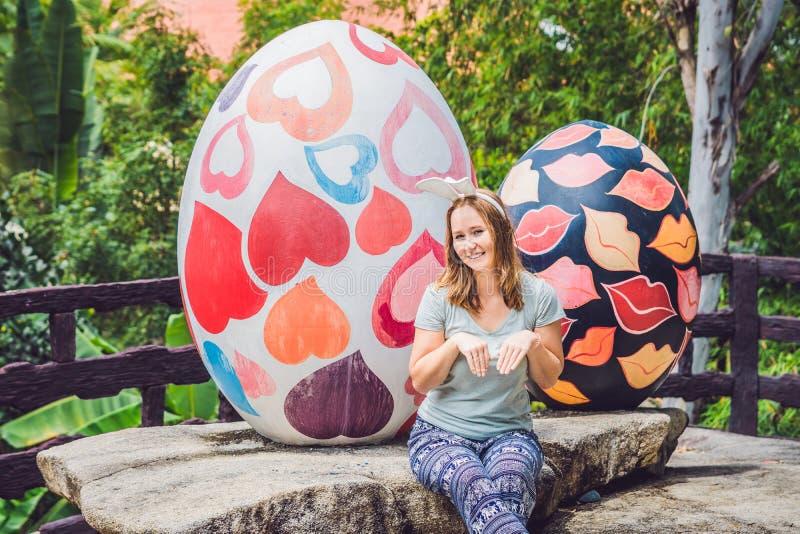 有获得兔宝宝的耳朵的美丽的少妇乐趣用传统复活节彩蛋寻找,户外 庆祝复活节假日 库存照片