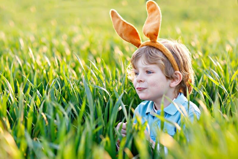 有获得兔宝宝的耳朵的逗人喜爱的小孩男孩乐趣用传统复活节彩蛋在温暖的晴天寻找,户外 免版税库存照片