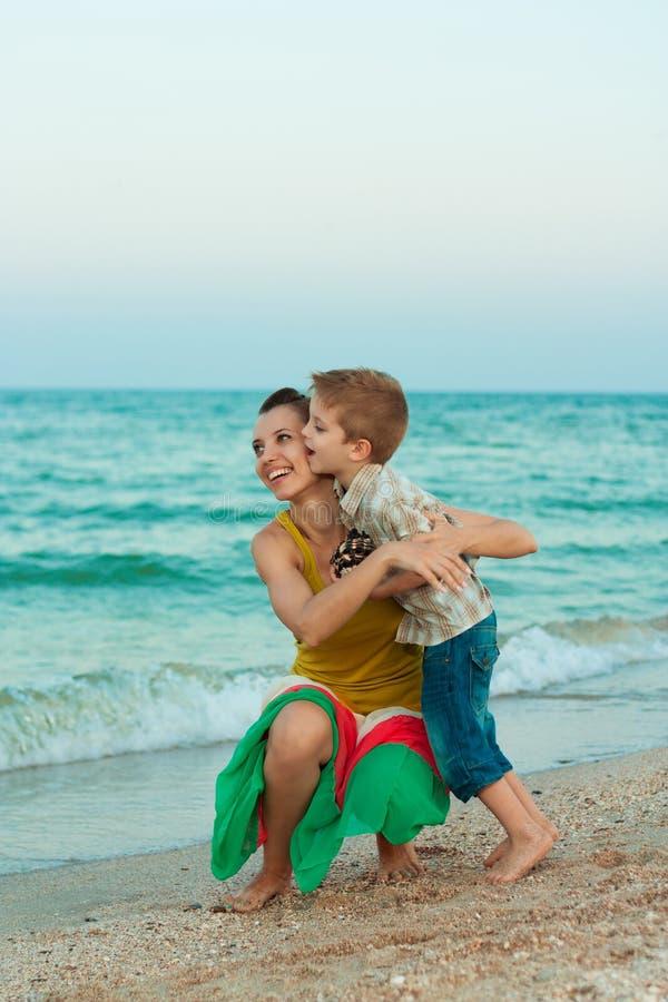 有获得她的儿子的年轻母亲在海滩的乐趣 库存图片