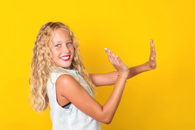 有获得完善的微笑的愉快的快乐的青春期前的女孩在黄色背景的乐趣 快乐有吸引力的可爱的俏丽的迷人的甜点 免版税库存照片