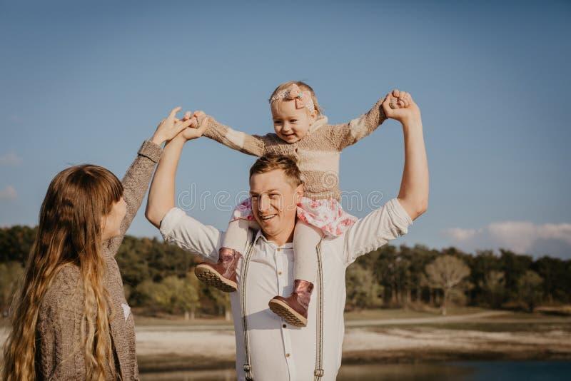 有获得的孩子的年轻家庭室外的乐趣 免版税库存照片
