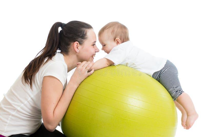 有获得的婴孩的母亲做体操和乐趣 免版税库存图片