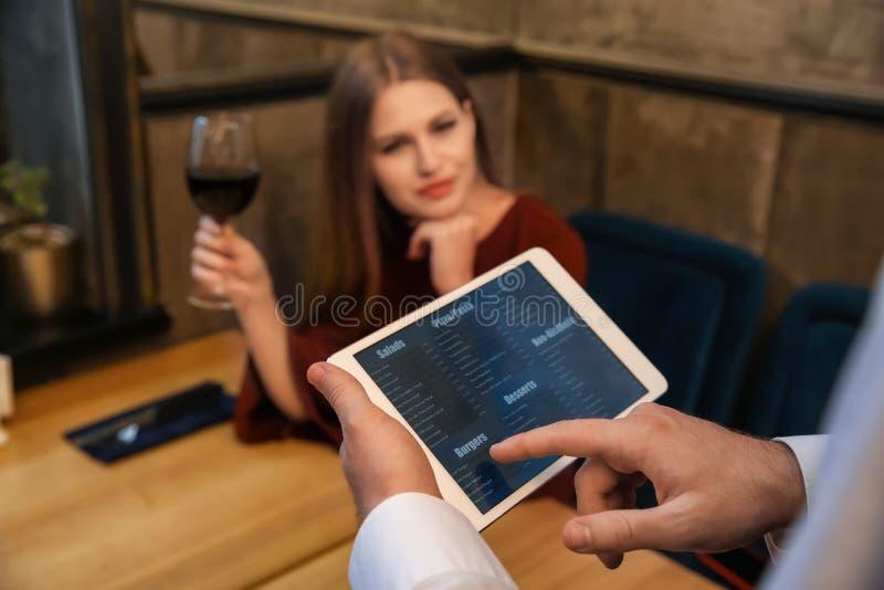 有菜单的年轻侍者在平板电脑屏幕上在餐馆 免版税库存照片