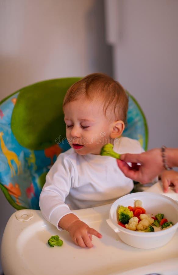有菜的哺养的婴孩-美丽的婴孩拒绝吃broc 库存照片