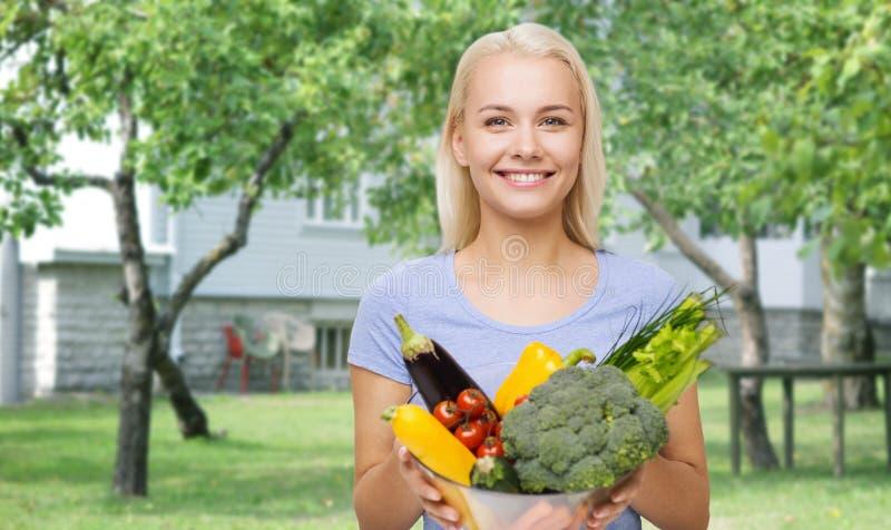 有菜的微笑的少妇在家庭菜园 免版税库存照片