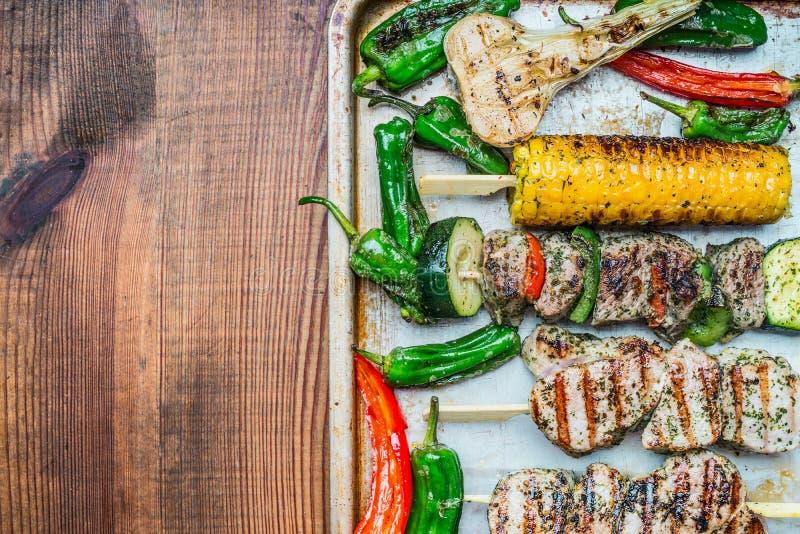 有菜的烤肉串和在烘烤盘子的烤玉米和土气木背景,顶视图,文本的地方 免版税库存照片