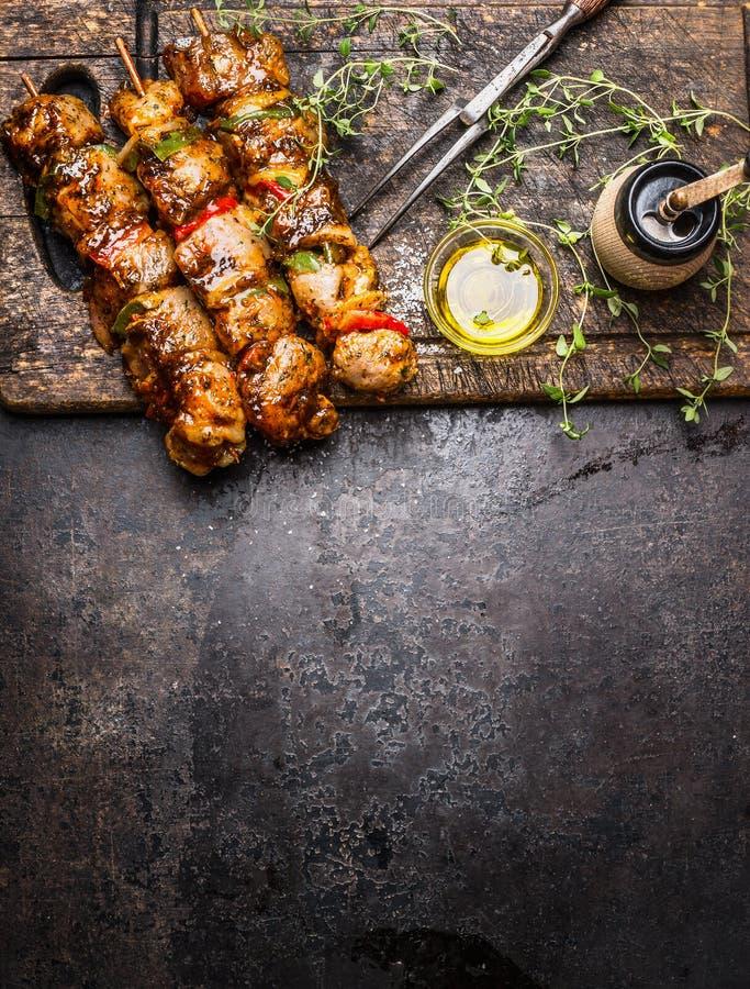 有菜的用卤汁泡的肉串格栅或BBQ的,在黑暗的土气木背景,顶视图的新鲜的晒干的nad油 免版税库存图片