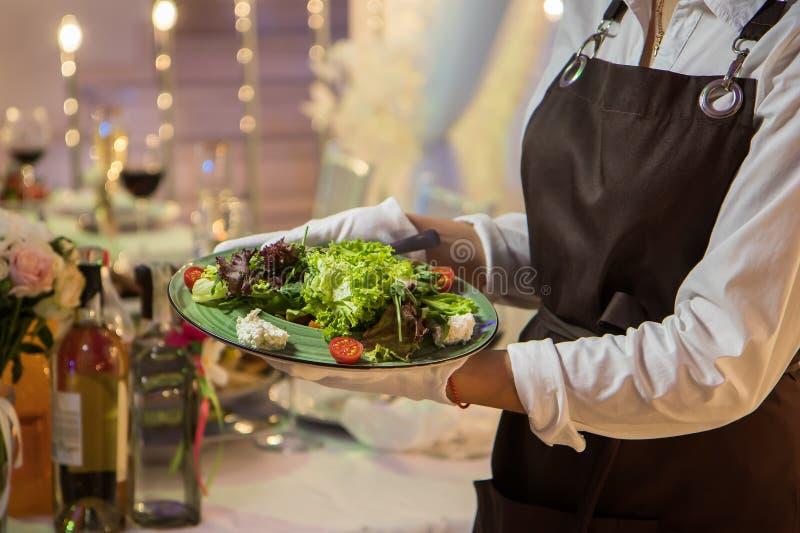 有菜食物盘服务宴会桌的女服务员 免版税图库摄影