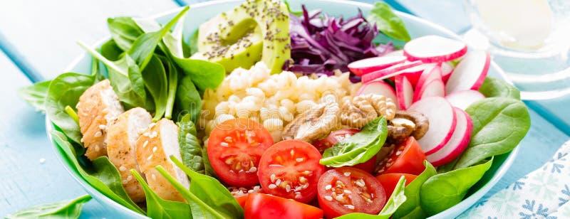 有萝卜、蕃茄、鲕梨、无头甘蓝和菠菜叶子烤鸡肉、碾碎干小麦和新鲜蔬菜沙拉的碗  健康a 免版税图库摄影