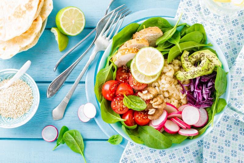 有萝卜、蕃茄、鲕梨、无头甘蓝和菠菜叶子烤鸡肉、碾碎干小麦和新鲜蔬菜沙拉的碗  库存照片
