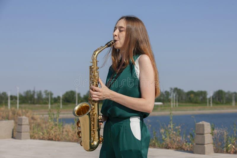 有萨克斯管的年轻女人在公园 免版税图库摄影