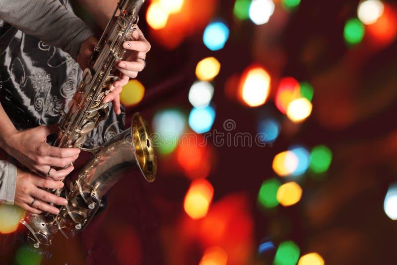有萨克斯管的男人的和妇女的手在bokeh光 免版税图库摄影