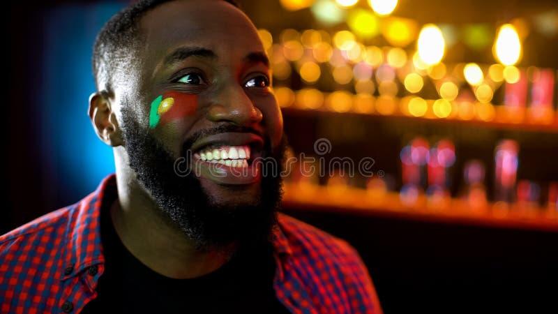 有葡萄牙旗子的快乐的黑人足球迷在面颊庆祝比赛胜利的 免版税库存照片