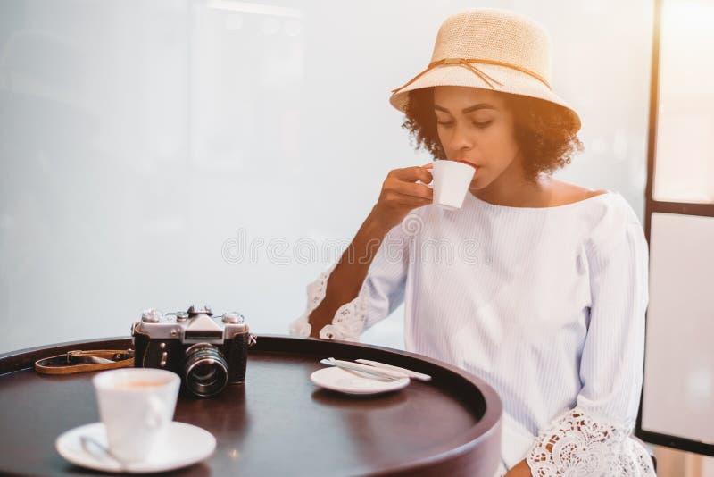 有葡萄酒凸轮的巴西女孩在咖啡馆饮用的咖啡 库存照片
