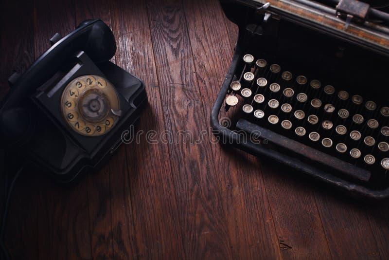 有葡萄酒打字机的老减速火箭的电话在木板 免版税库存图片