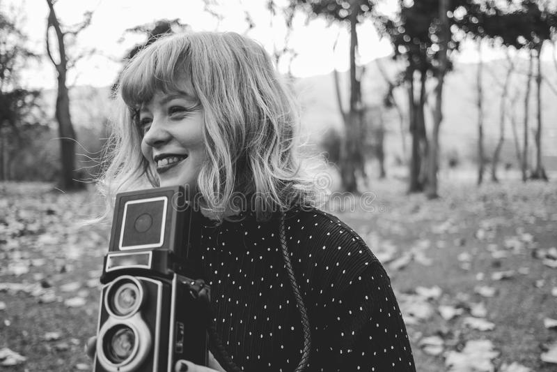 有葡萄酒样式衣裳和照相机的美丽的少妇 免版税库存图片