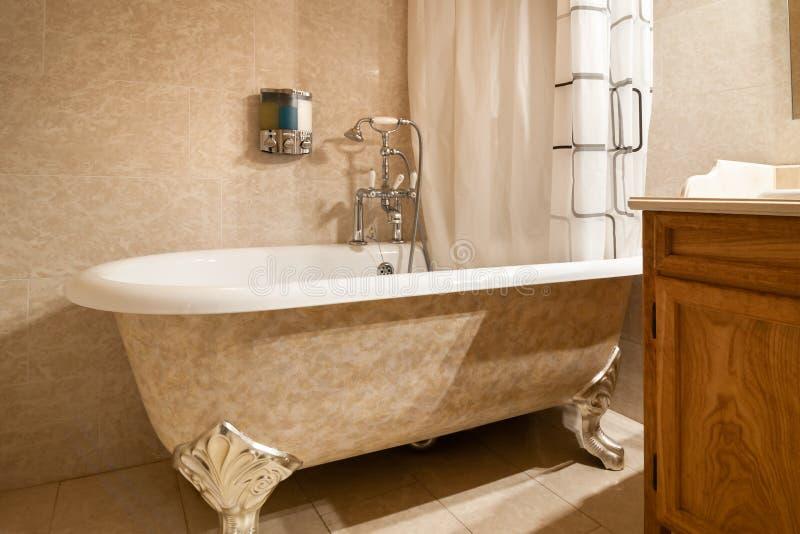 有葡萄酒浴缸装置的浴缸与灵活的淋浴喷头 免版税库存图片