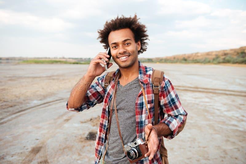 有葡萄酒照片照相机的愉快的人谈话在手机 库存照片