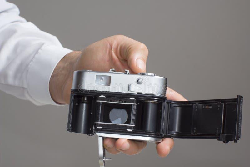 有葡萄酒照相机的人的手 免版税库存图片
