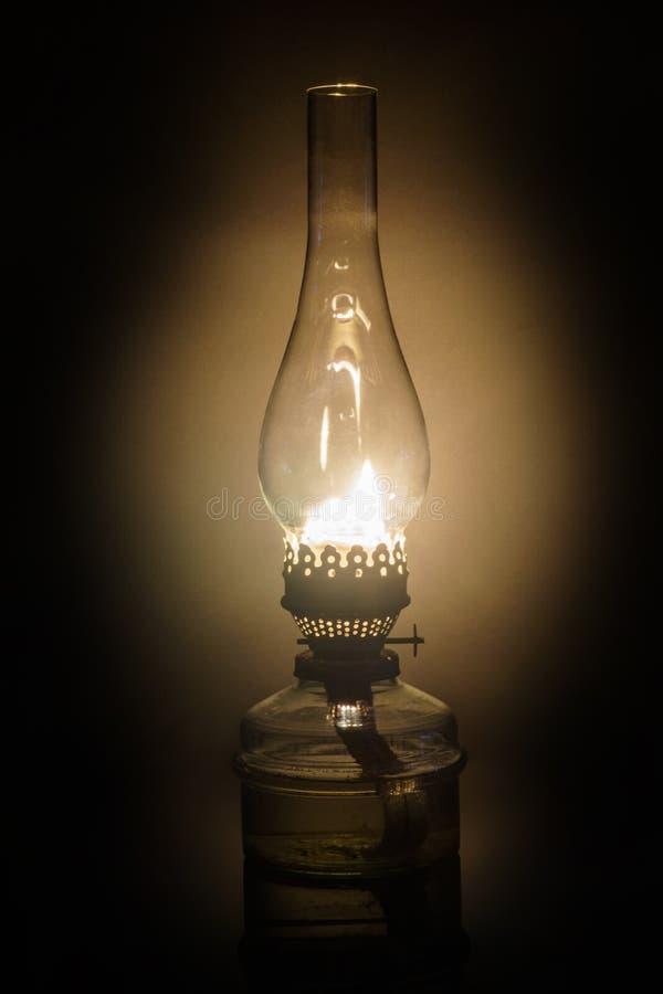 有葡萄酒玻璃烟囱的发光的古色古香的老煤油油灯 免版税库存图片