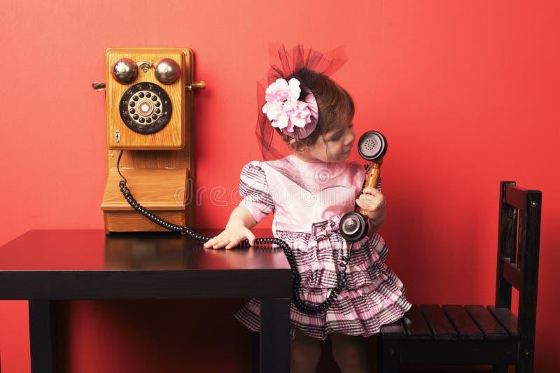 有葡萄酒电话的小女孩 库存图片