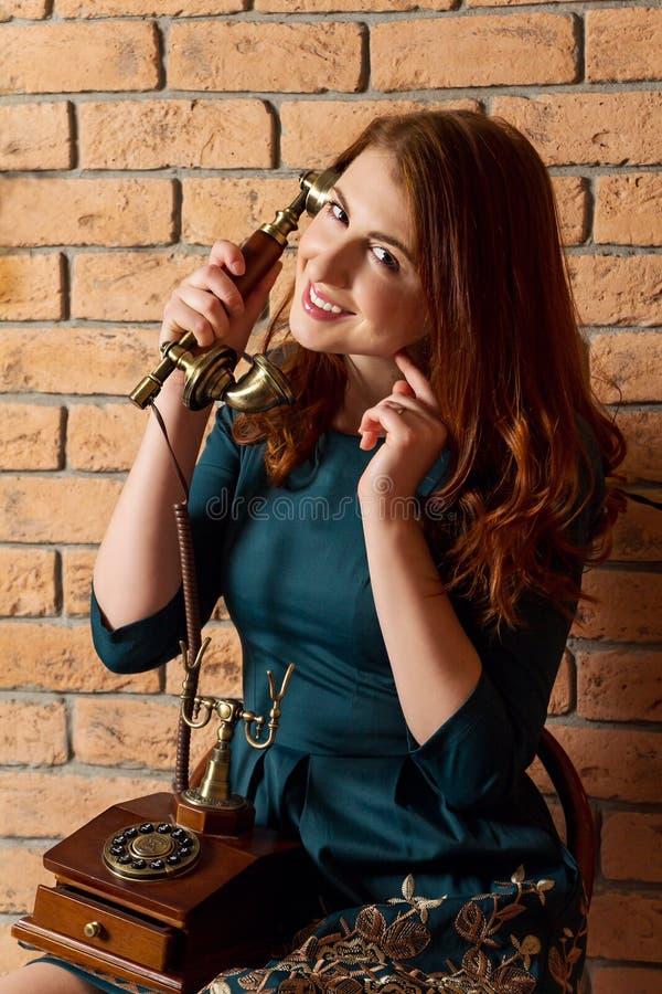 有葡萄酒电话的微笑的女孩 库存照片