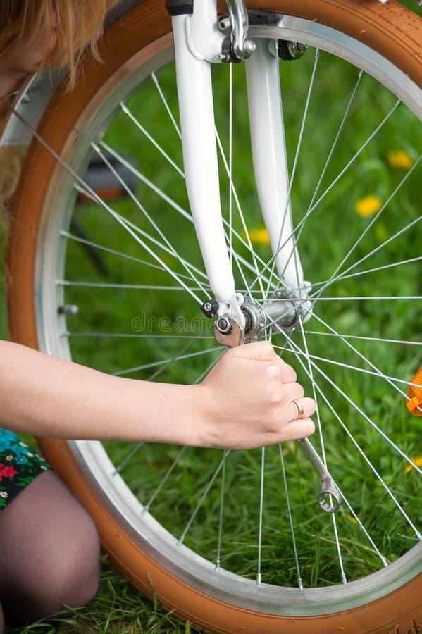 有葡萄酒白色自行车的女性骑自行车者在春天庭院里 免版税库存照片